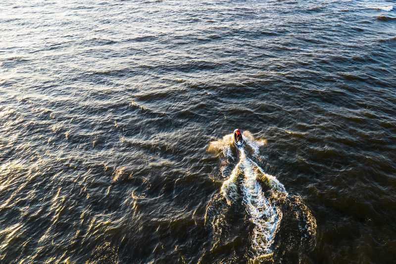 Aerial view of man rides on fast water scooter jumping on waves and making golden splashes on sunset