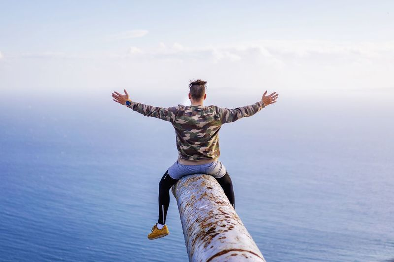 Rear view of man sitting with arms outstretched on rusty metallic pipe while looking at sea against sky