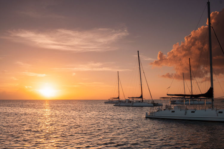 Sunset Water Sky Nautical Vessel Transportation Sailboat Sea Cloud - Sky Mode Of Transportation Beauty In Nature Pole Sun Mast Nature Scenics - Nature Tranquil Scene Orange Color Tranquility No People Horizon Over Water Outdoors Yacht Catamaran Copy Space Vacations