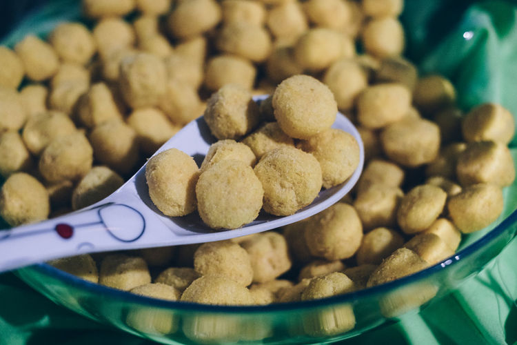 scoop of crunchy finger food corn balls in a glass bowl Food And Drink Food Close-up Still Life Large Group Of Objects No People Eating Utensil Container Bowl Spoon Selective Focus Abundance Focus On Foreground Healthy Eating Indulgence Snack Breakfast Temptation Personal Perspective Corn Processed Food Spicy Balls Crunchy Party