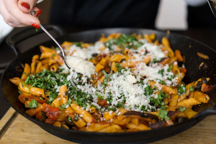 Close-Up Of Hand Holding Spoon Over Pasta