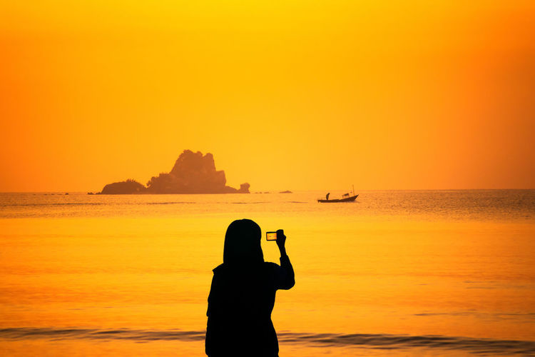 Silhouette man on sea against sky during sunset