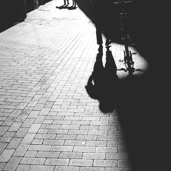 Shadow Silhouette Sunlight Day Black And White Black And White Photography Shadow Photography Shadows & Light Shadow Of A Bike And A Person Bike Man Walking Little Shadow Of Two People Road Structure Man Walking Beside His Bike