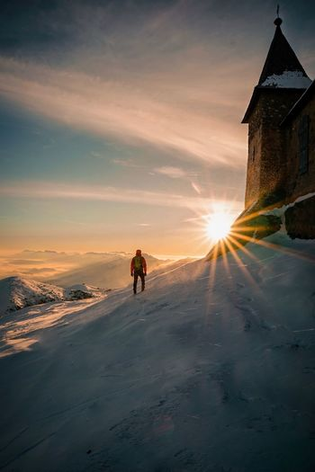 Man on snow amidst buildings against sky during sunset