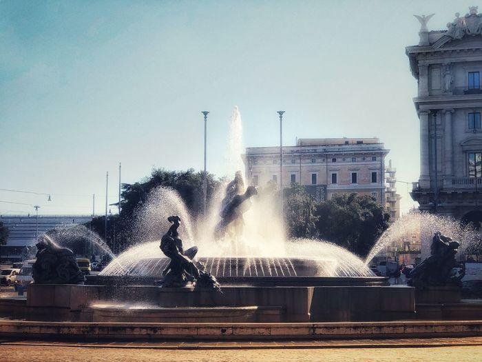 Fountain in city against clear sky