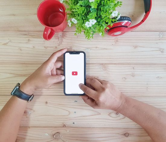 Youtube Music Wireless Technology Communication Smart Phone Portable Information Device Adult Technology Human Hand Red Wood - Material Healthy Eating Internet Mobile Phone Indoors