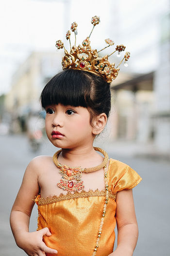 Close-Up Of Cute Girl Wearing Orange Dress And Crown