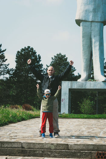 Portrait Of Father And Son With Arms Raised Standing At Park Against Sky
