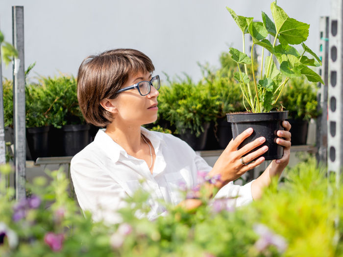 Young woman sitting on potted plant