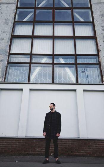 Full length of man looking through window in building