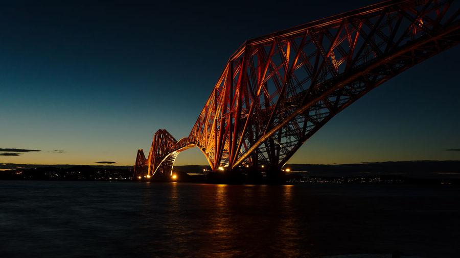 The Forth Bridge crossing the Firth of Forth illuminated at late sunset, Edinburgh, Scotland. Edinburgh Firth Of Forth Forth Rail Bridge Scotland Sir Benjamin Baker. Sir John Fowler Unesco World Heritage Site Bridge Cantilever Cantilever Span Construction Engineering Illuminated Impressive Railway Railway Bridge River Crossing Sunset Sky Bridge - Man Made Structure Connection Architecture Built Structure Night Water Waterfront Transportation Nature Travel Destinations River Low Angle View Clear Sky Travel Outdoors Bay