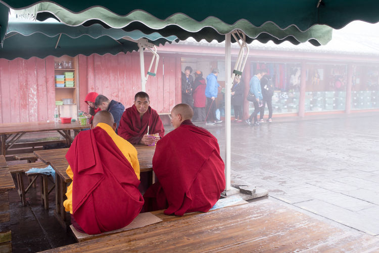 Three Tibetan monks eating instant noodle in cold foggy weather. Buddhist Eating Lifestyle Red Tourists Weather Brown Cold Cultures Foggy Food Instant Noodle Monks People Religion Resting Simple Tibet Tibetan  Traditional Clothing Warm Yellow