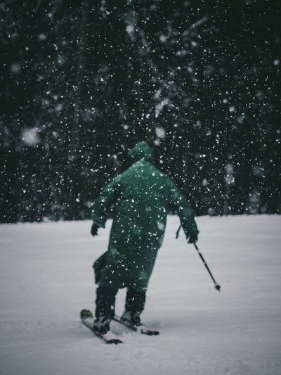 Rear view of man skiing on snow covered field during snowfall