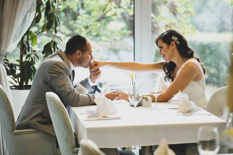 Young wedding couple sitting on table