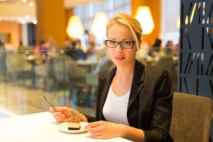 Portrait of smiling woman eating while sitting at restaurant