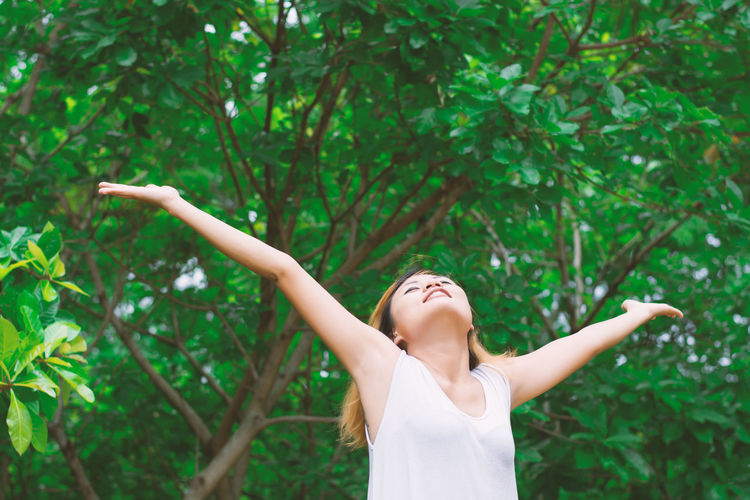 Woman With Arms Outstretched Standing Against Trees