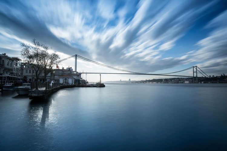 Bosphorus bridge over river by buildings against sky