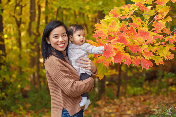 Mother and daughter in park during autumn