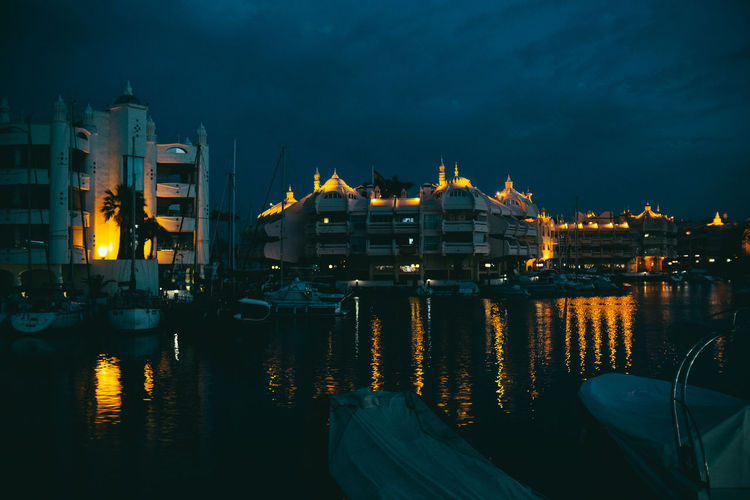 Sailboats moored on illuminated buildings in city at night