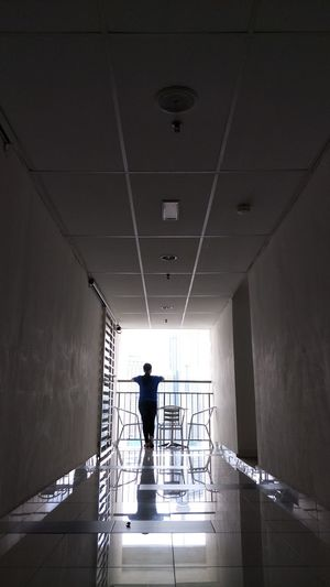 A shot of a woman from behind standing at a balcony facing skyscrapers on a daylight Chairs And Table Skyscrapers Alone Standing Alone Woman Lonely Woman Apartment Hallway Balcony Shot City Full Length Standing Silhouette Shadow Human Back Rear View
