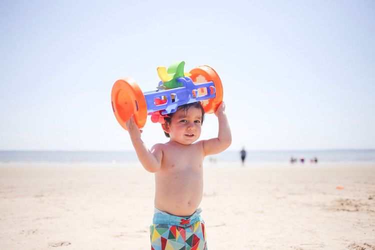 Portrait of shirtless boy carrying plastic toy on head at beach