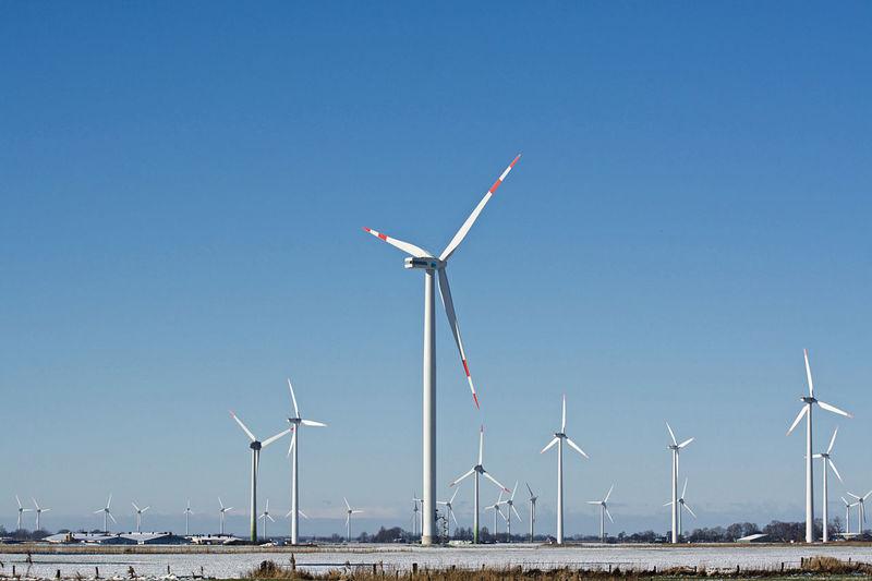 Windmills on field against clear blue sky
