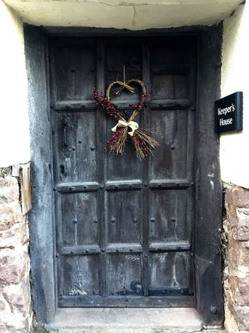 Dunster Medieval Doorway Nature Text Hanging Weathered Outdoors Window House No People Building Closed Building Exterior Entrance Wall - Building Feature Architecture Old Built Structure Safety Metal Door Day