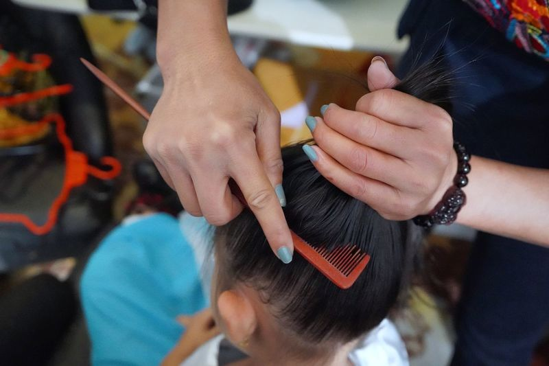 Midsection of mother combing hair of daughter at home