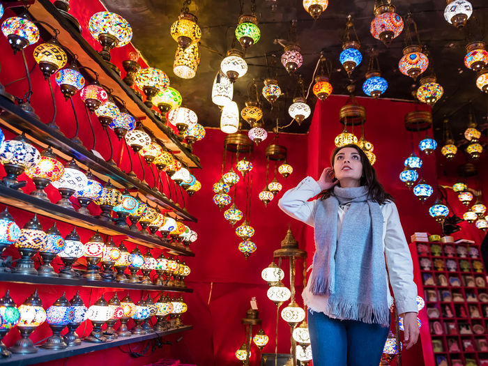 Low angle view of woman standing by illuminated lanterns