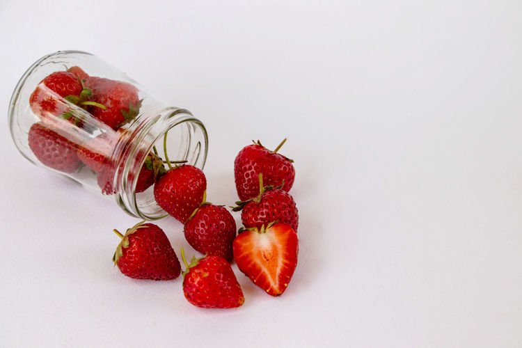 High angle view of strawberries on glass against white background