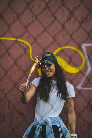 Portrait of young woman holding distress flare against wall