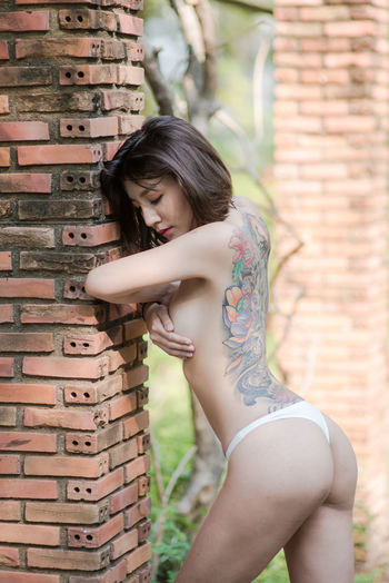Side view of topless young woman with tattoo standing against brick wall