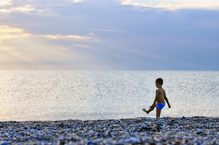 Angry boy is kicking of the beach stones into the sea. Angry Boy Beautiful Dusk Beautiful Sunset Bored Boy Boredom Boys Childhood Children Only Cloud - Sky Horizon Over Water Keep Calm Kicking Kicking It Loneliness Peaceful Place Pissed Off  Scenics Sunlight Rays Sunset