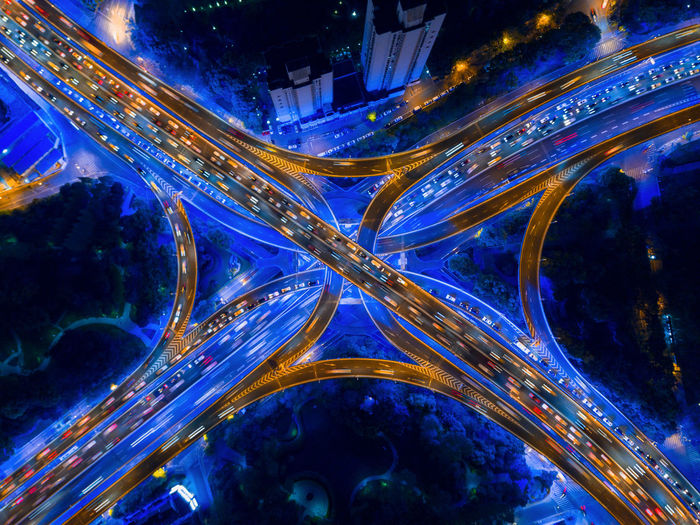 Aerial view of highway junctions shape letter x cross at night. Bridges, roads, or streets in connection or transportation concept. Structure of architecture in urban city, Shanghai Downtown, China. Shanghai China City Road Downtown District Financial District  Architecture Landmark Landscape Building Highway Expressway Illuminated No People Night Connection Motion Built Structure Abstract Speed Modern Long Exposure Technology Pattern Building Exterior Glowing Futuristic High Angle View Nature Outdoors Cityscape Digital Composite Multiple Lane Highway