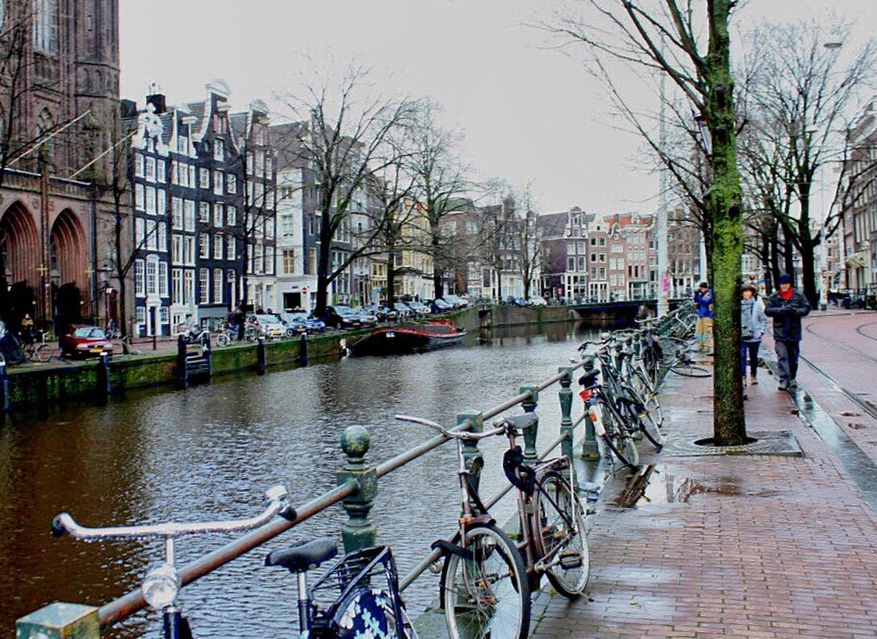 architecture, built structure, city, building exterior, transportation, mode of transport, canal, city life, bare tree, bicycle, travel destinations, outdoors, bridge - man made structure, water, day, nautical vessel, large group of people, tree, people, cityscape, gondola - traditional boat, sky