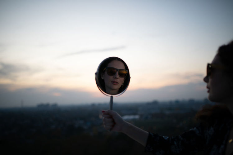 Reflection of woman wearing sunglasses in mirror against sky during sunset
