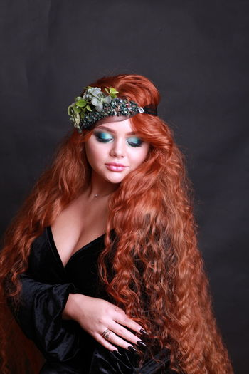 Sensuous Young Woman Wearing Wreath Against Black Background