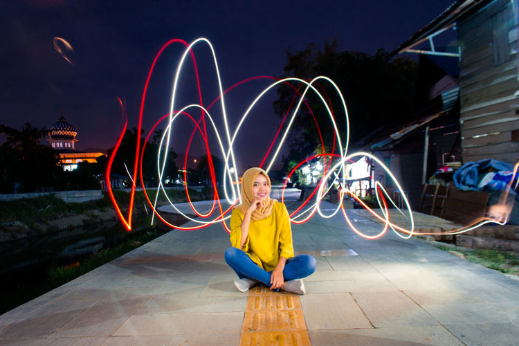 Woman sitting against light trail at night