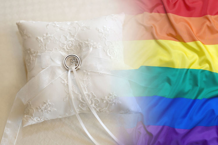 Double Exposure Of Rainbow Flag And Wedding Rings