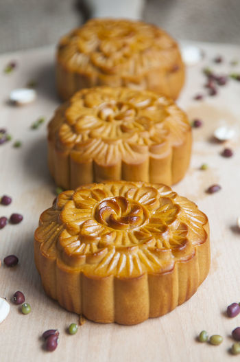 High angle view of moon cakes arranged with seeds on cutting board