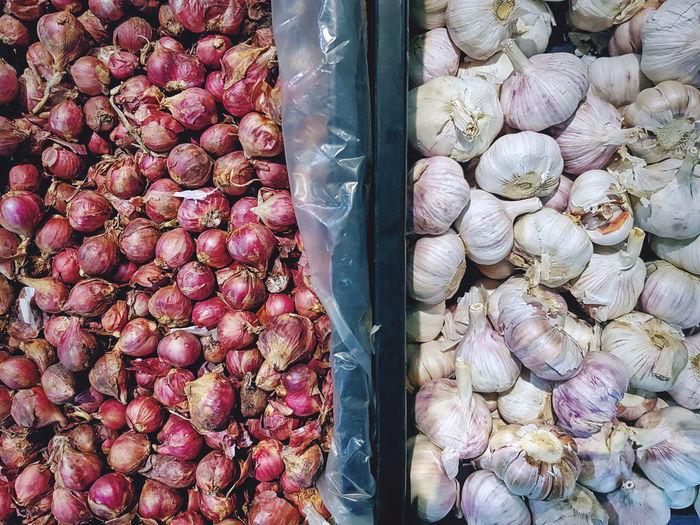 Piles of fresh onion shallots and garlic