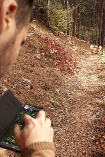 Midsection of man photographing in forest