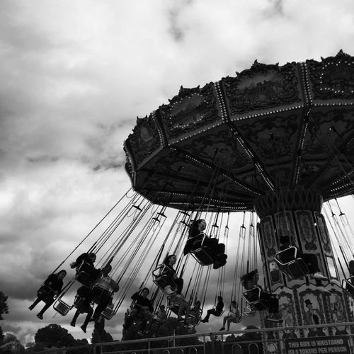 Amusement Park Arts Culture And Entertainment Amusement Park Ride Leisure Activity Enjoyment Carousel Sky Low Angle View Fun Outdoors Day Men Real People Merry-go-round Carousel Horses Lifestyles Large Group Of People Sitting Group Of People Women