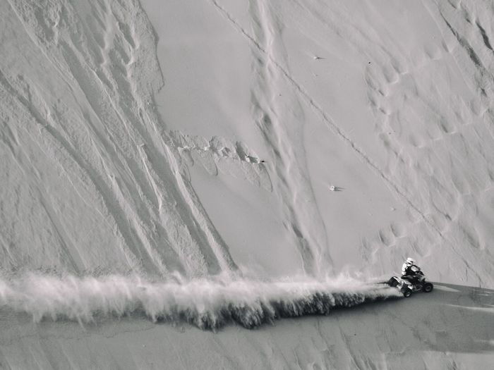 High Angle View Of Person Riding Quadbike On Sandy Field