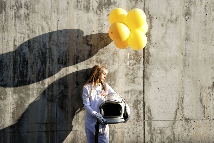 Side view of a young woman holding balloons