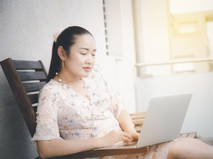 Woman looking at camera while sitting in laptop