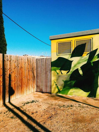 Graffiti on cabin by wooden fence against clear blue sky