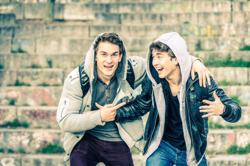 Young hipster brothers having fun with each other - Best friends sharing free time together in urban area outdoors - Handsome guys with winter fashion hoodie clothes enjoying everyday life moments Best  Brotherhood Brotherliness Brotherly Brothers Casual Clothes Community Concept Cool Desaturated Everyday Excited Fashion Fashionable Feeling Filter Fraternity Friends Friendship Fun Grunge Guys Happy Jeans Lifestyle Male Men People Playful Retro Similar Sweater Sweatshirt Teenagers  Teens Travel Trendy Twins Understanding Urban Vintage Wardrobe Weekend Young Youngster Youth Millenials Millennials Gen Z