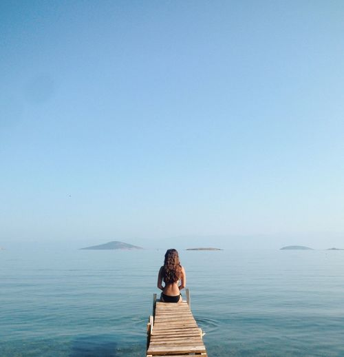 Rear view of woman sitting on pier over sea against clear sky
