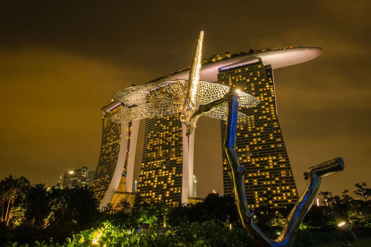 Low Angle View Of Sculpture Against Marina Bay Sands In City At Night